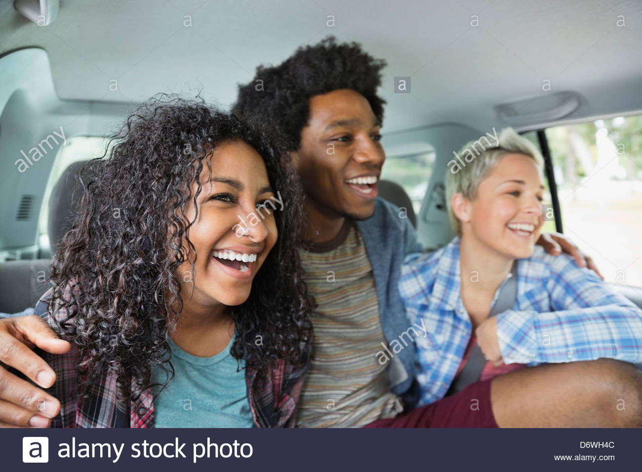 Happy young man with arms around female friends sitting in truck - Stock Image