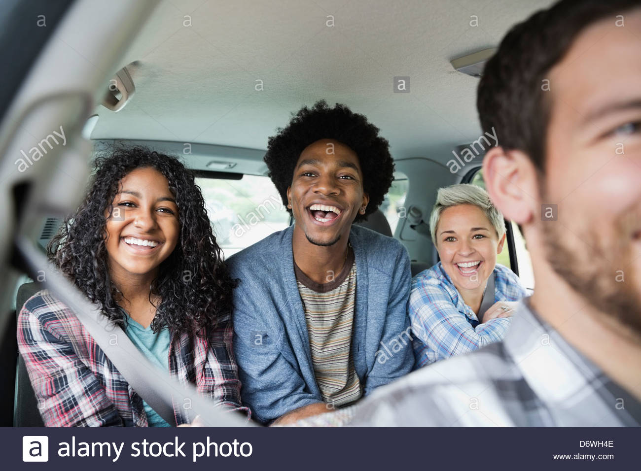 Portrait of happy teenage girl enjoying road trip with friends in truck - Stock Image