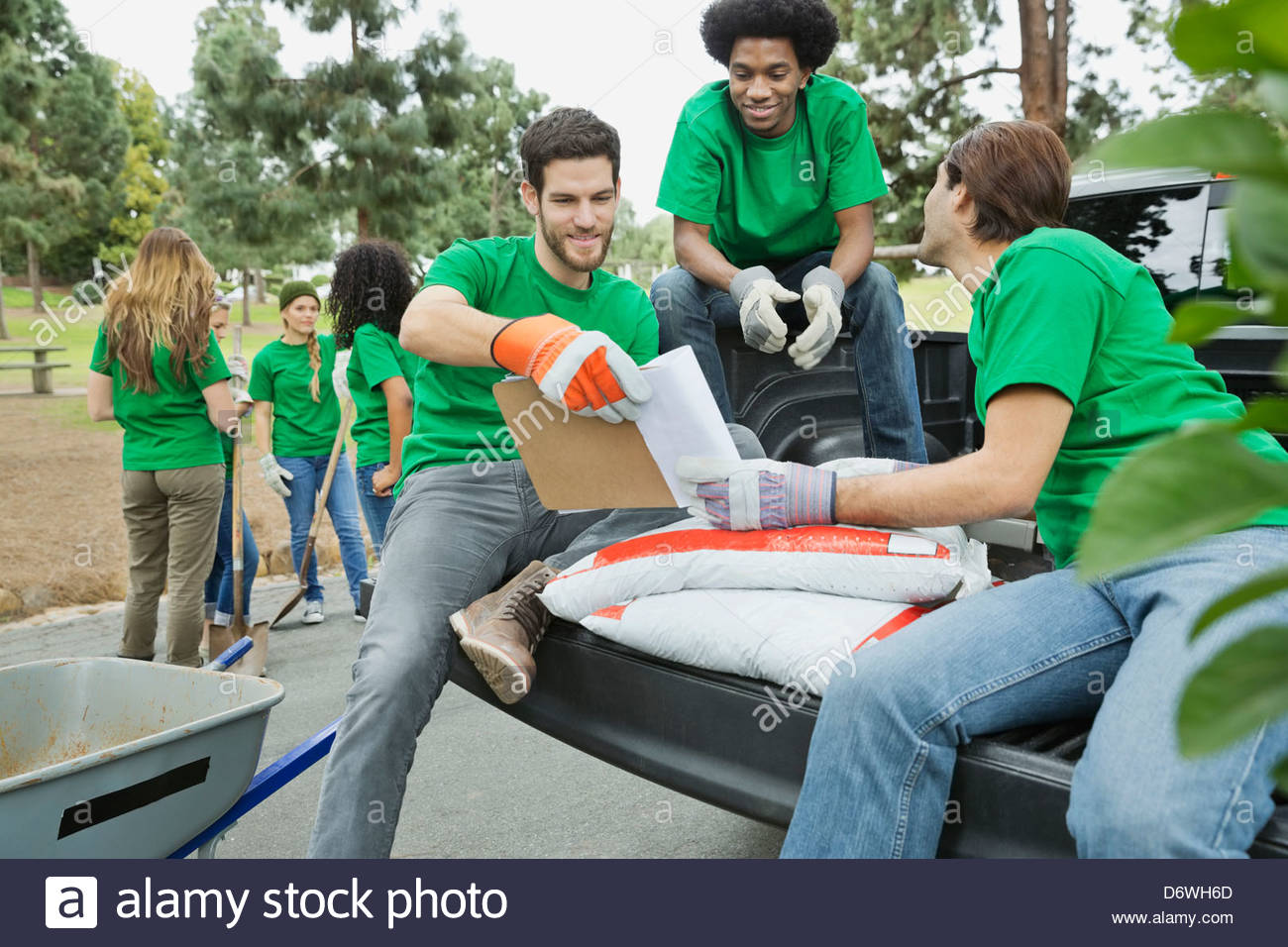 Male environmentalists reviewing checklist with friends in background - Stock Image