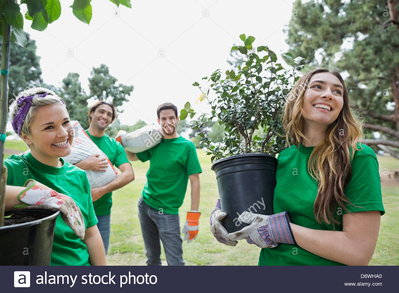 Happy environmentalists with potted plants and soil sacks at park - Stock Image