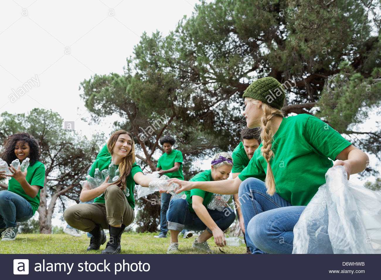 Group of happy environmentalists collecting plastic bottles in park - Stock Image