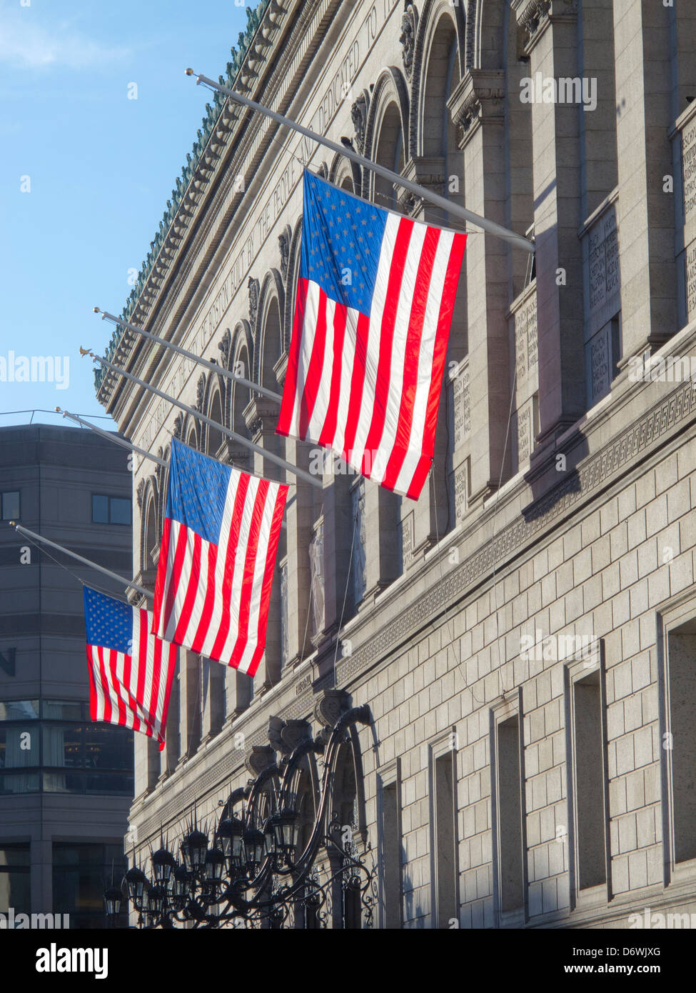 American flags dangle in the sun from the Boston Public Library, Copley Square, Boston, Massachusetts, USA - Stock Image