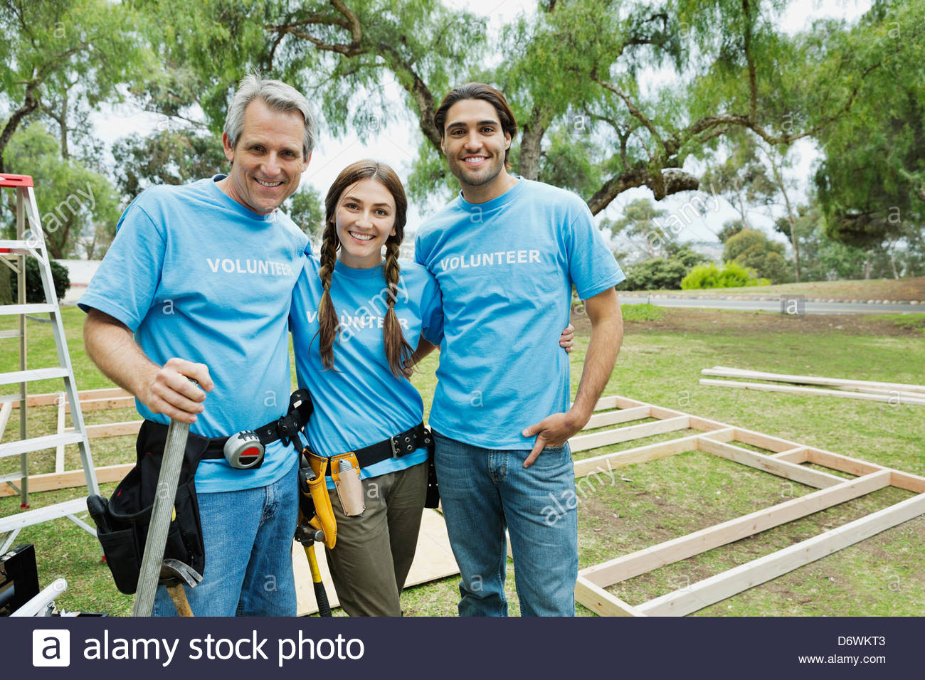 Portrait of three confident volunteers standing at construction site - Stock Image