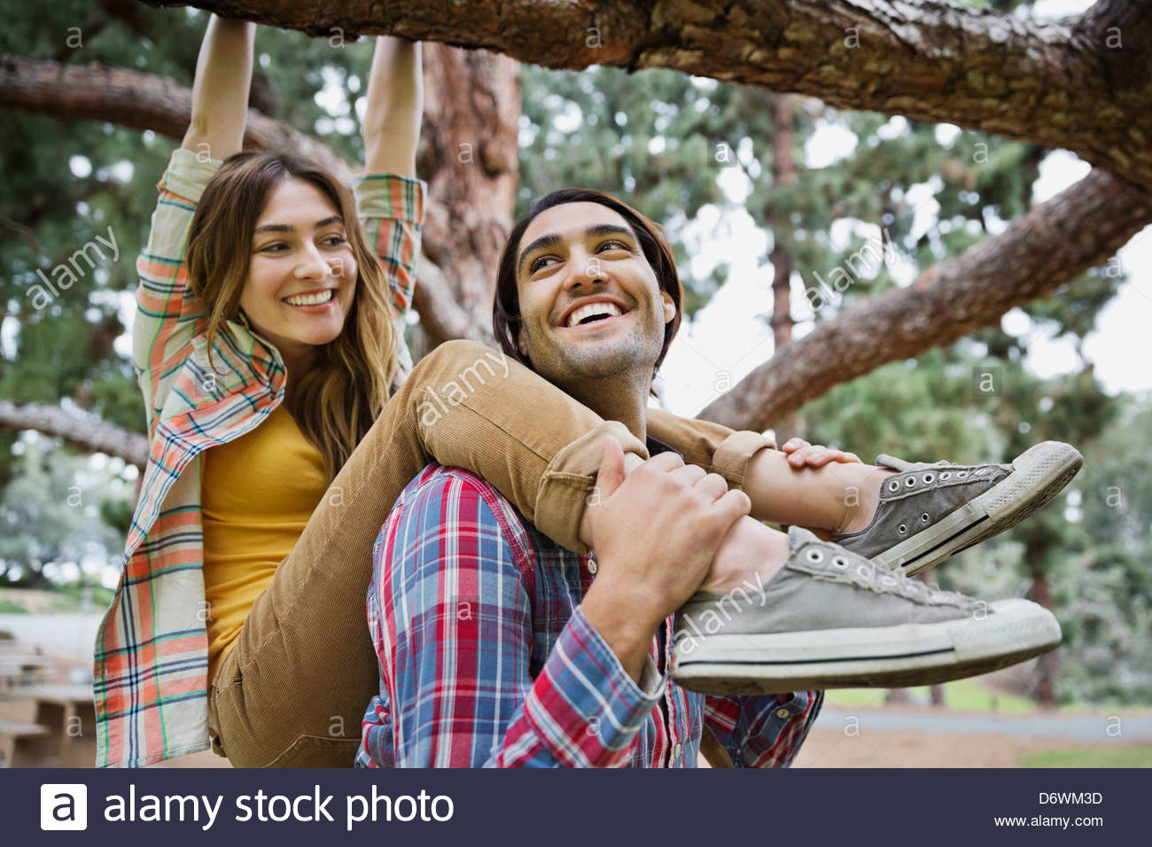 Happy young man supporting woman hanging on tree branch in park - Stock Image