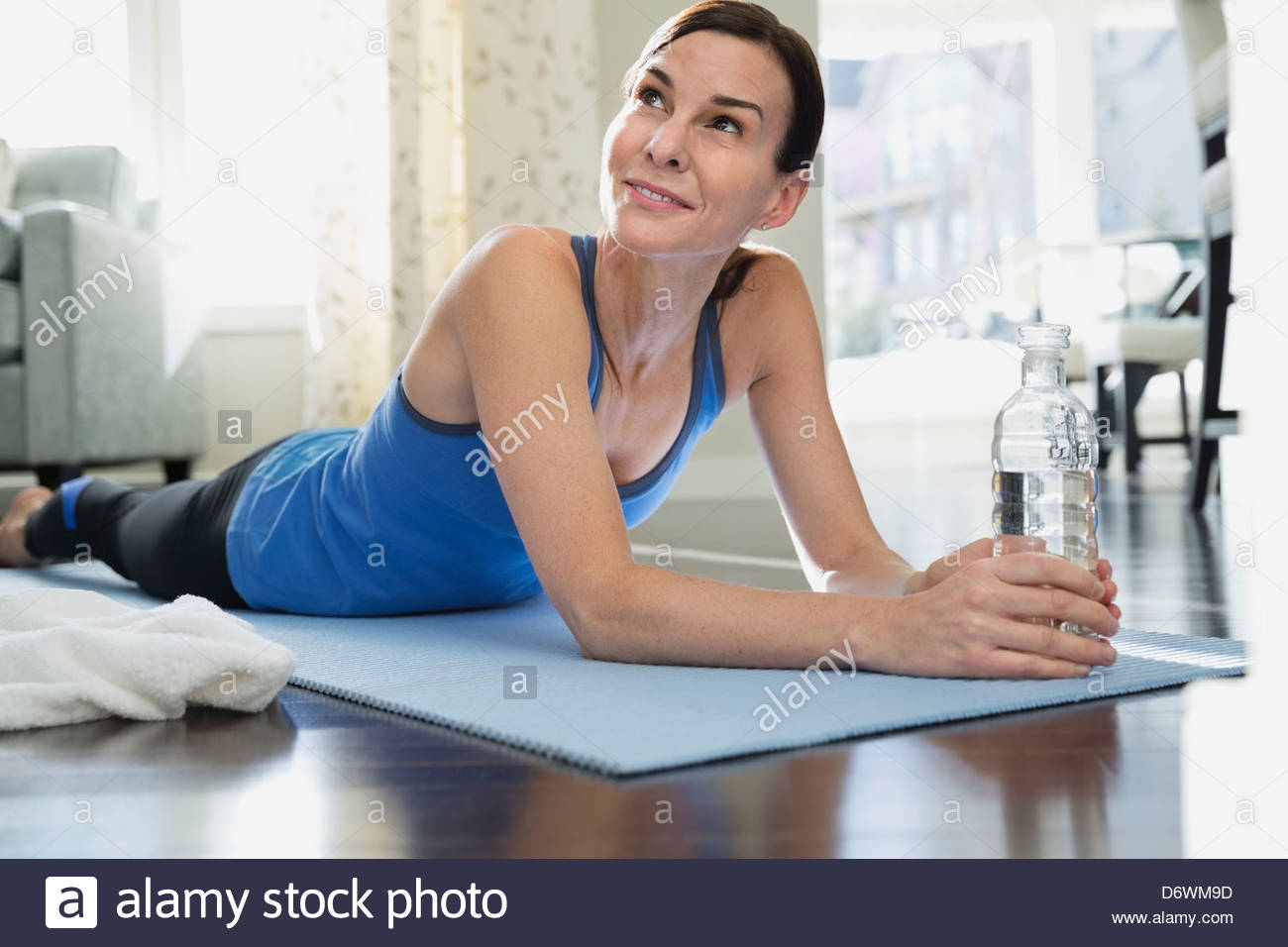 Thoughtful happy mature woman resting on exercise mat - Stock Image