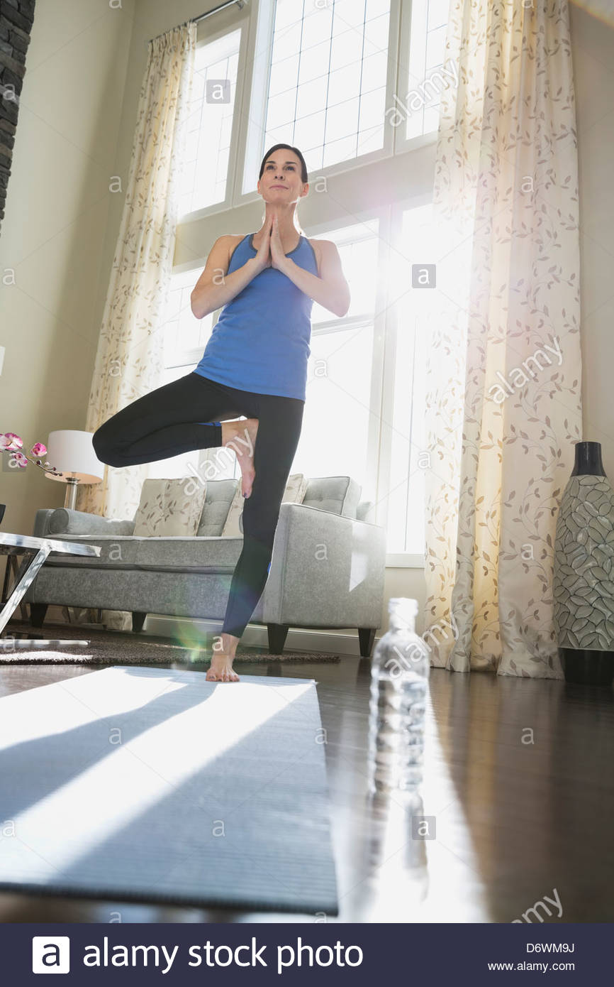 Mature woman performing tree pose at home - Stock Image