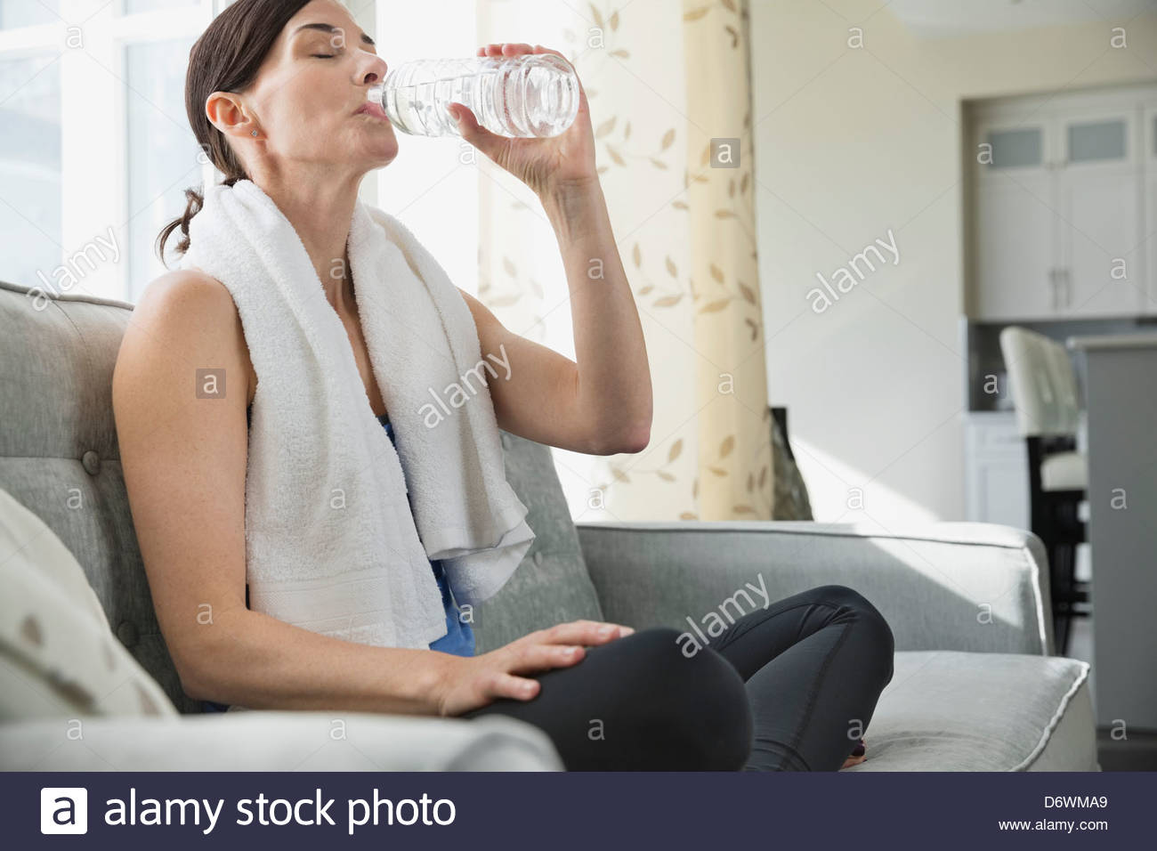 Mature woman drinking water from bottle on sofa - Stock Image