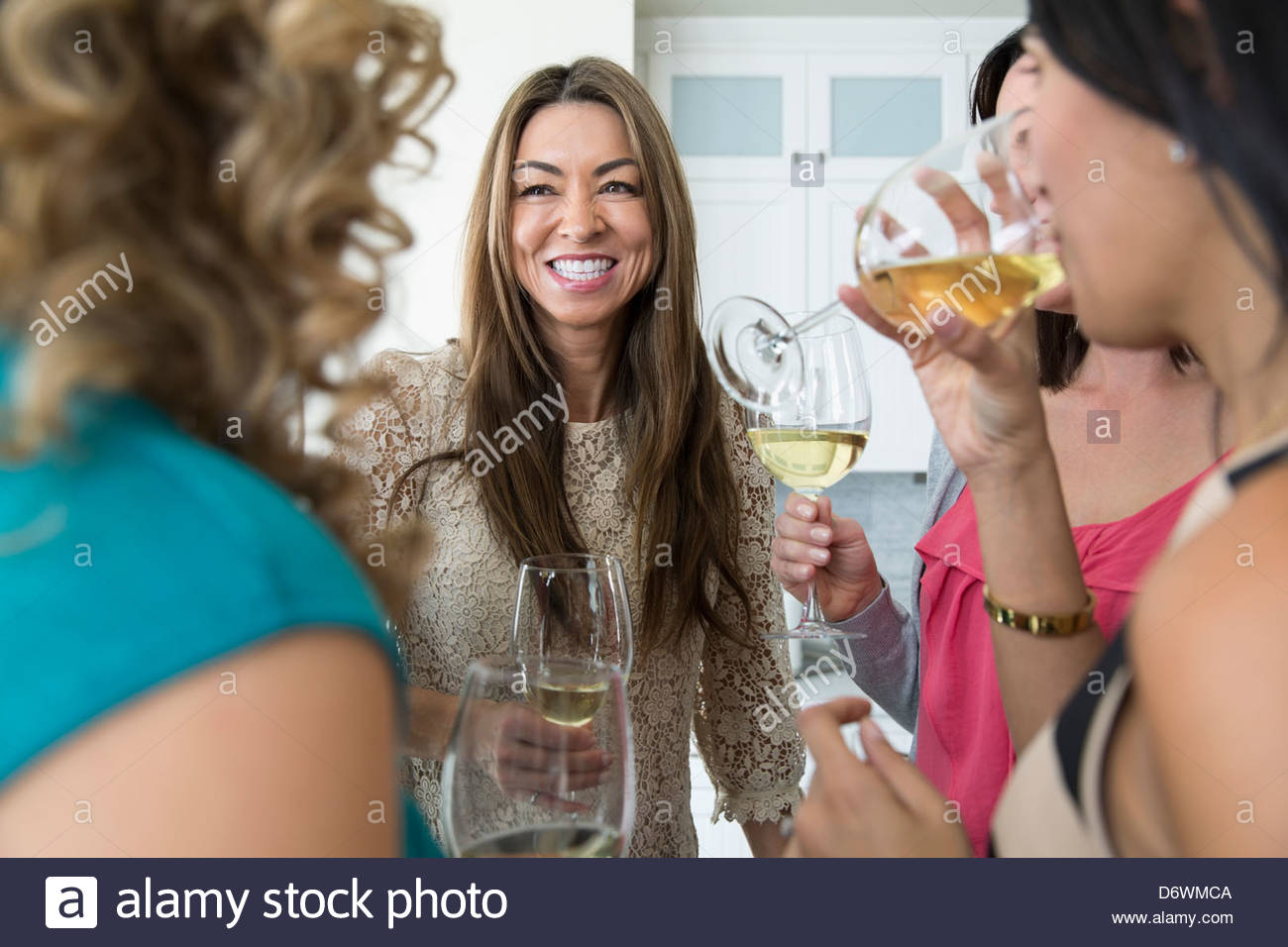 Happy mature woman with female friends enjoying house party - Stock Image