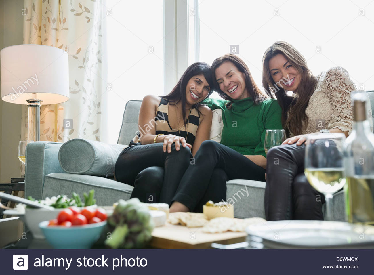 Happy mature women enjoying house party with food in foreground - Stock Image
