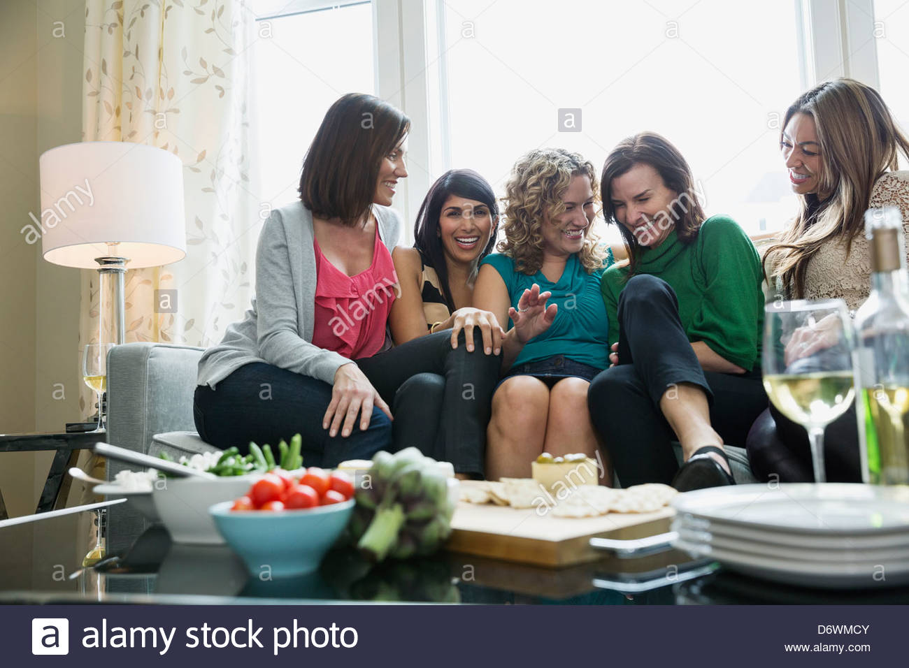 Portrait of happy woman with female friends enjoying house party - Stock Image
