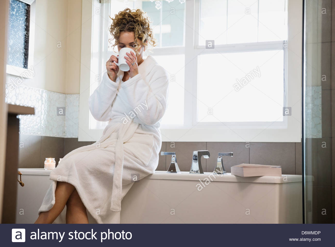 Mature woman in bathrobe drinking coffee while sitting on bathtub - Stock Image
