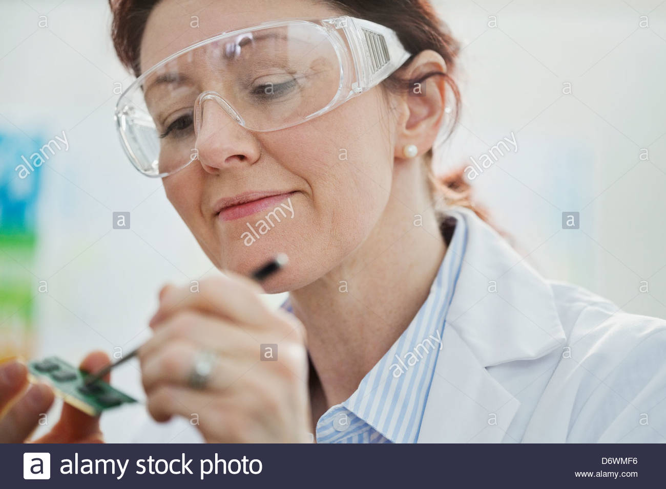 Female lab technician testing micro-chip - Stock Image