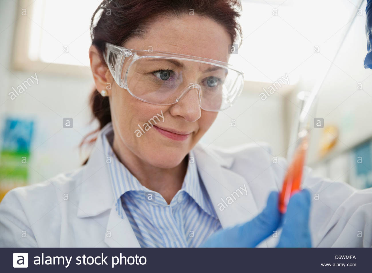 Close-up of female lab technician testing sample in test tube - Stock Image