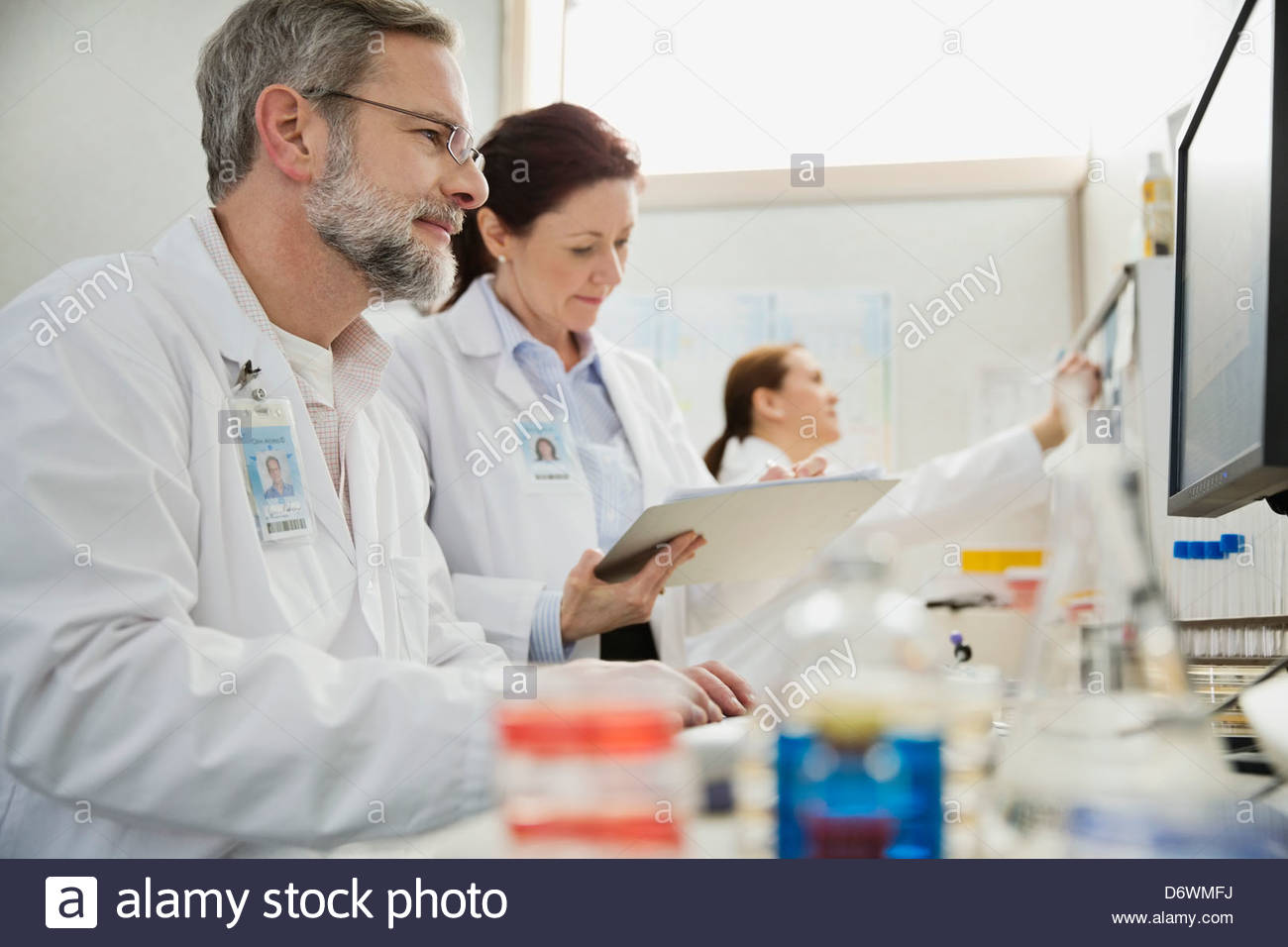 Mature male and female medical professionals working in lab - Stock Image