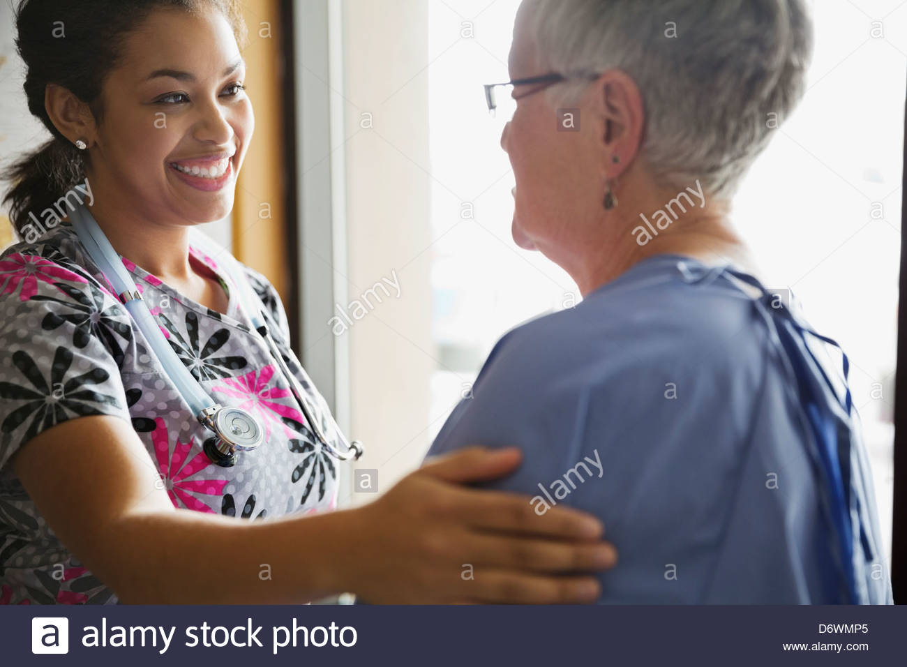Young female doctor comforting patient in clinic - Stock Image