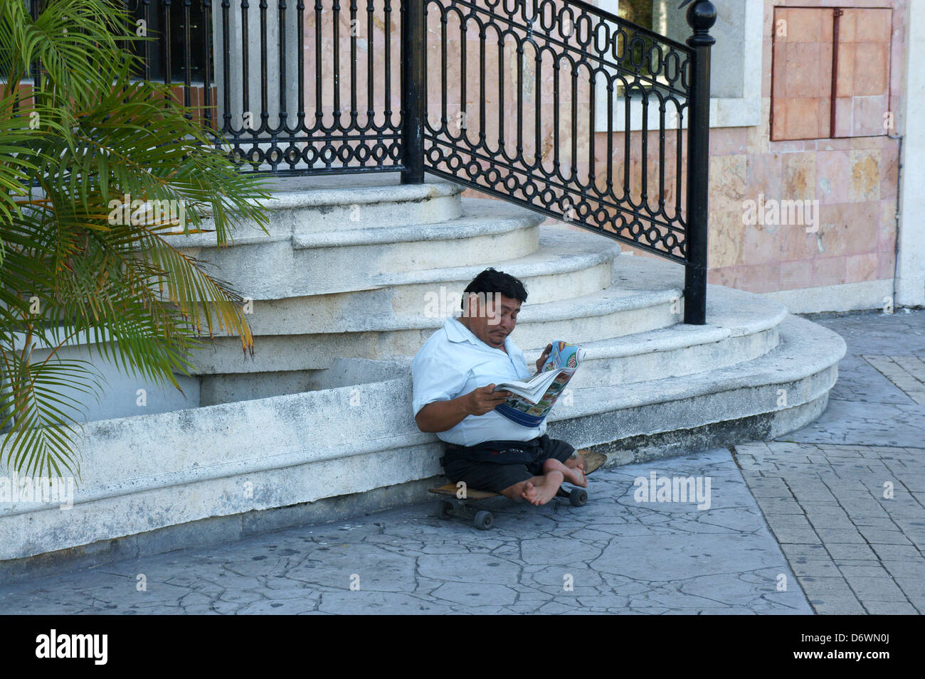 Mexican man with deformed legs and feet sitting on a skateboard and reading a newspaper, Cancun, Quintana Roo, Mexico - Stock Image