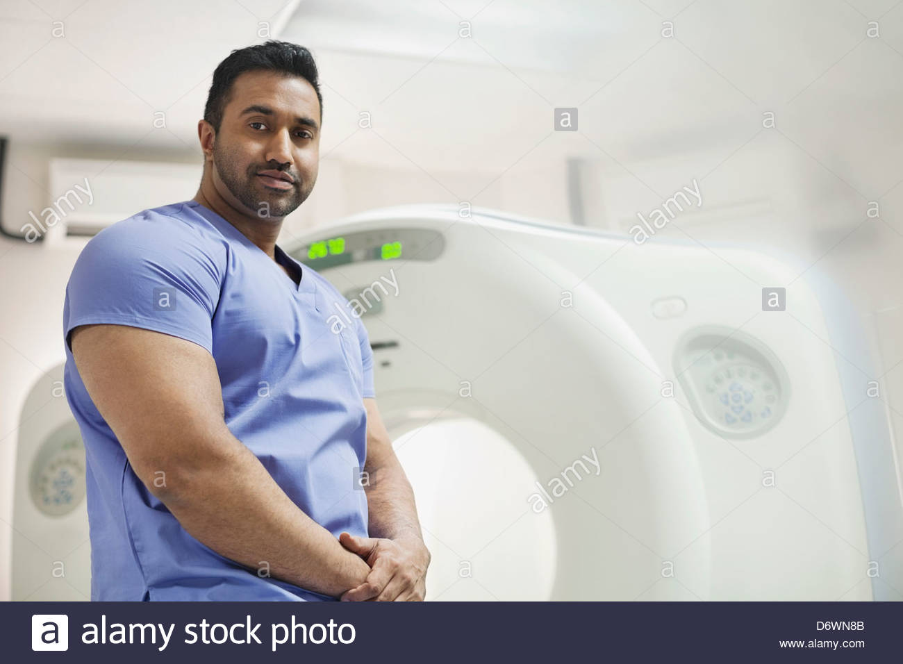 Portrait of mid adult male radiologist in front of CAT scan machine - Stock Image
