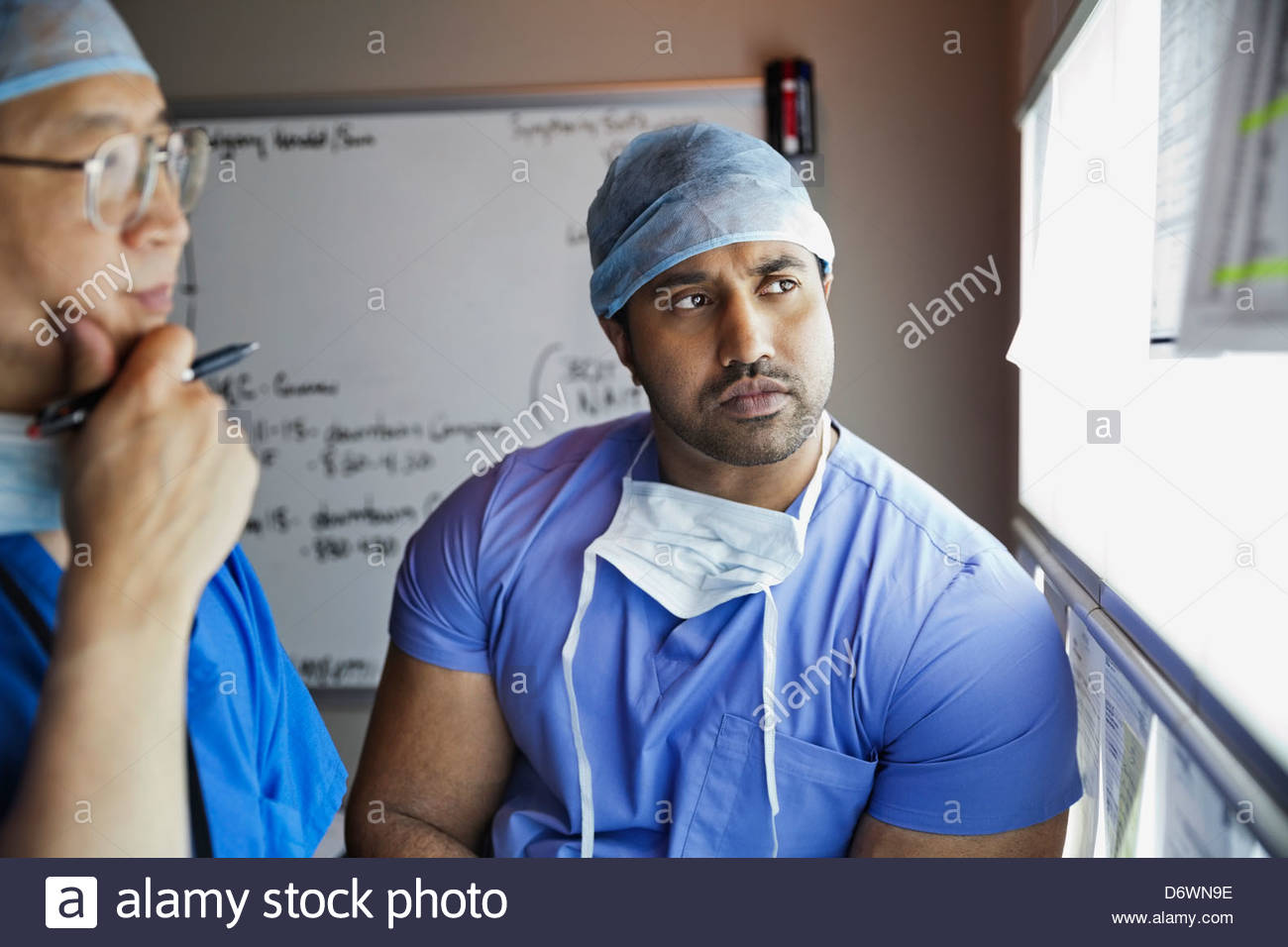 Senior surgeon and doctor examining report in hospital - Stock Image