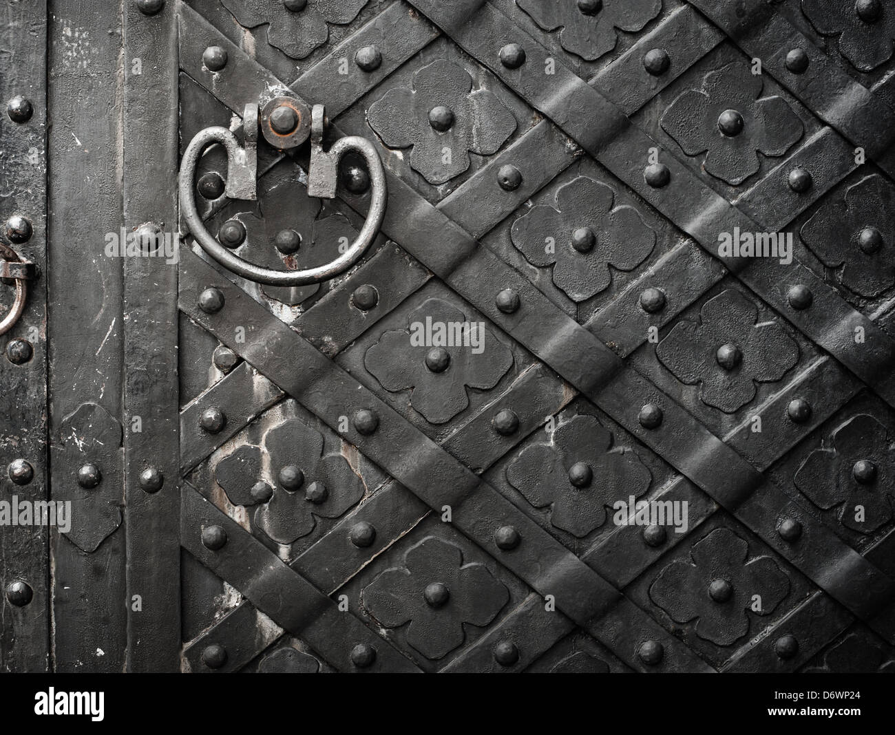 Old black door with rivets and flower pattern - Stock Image
