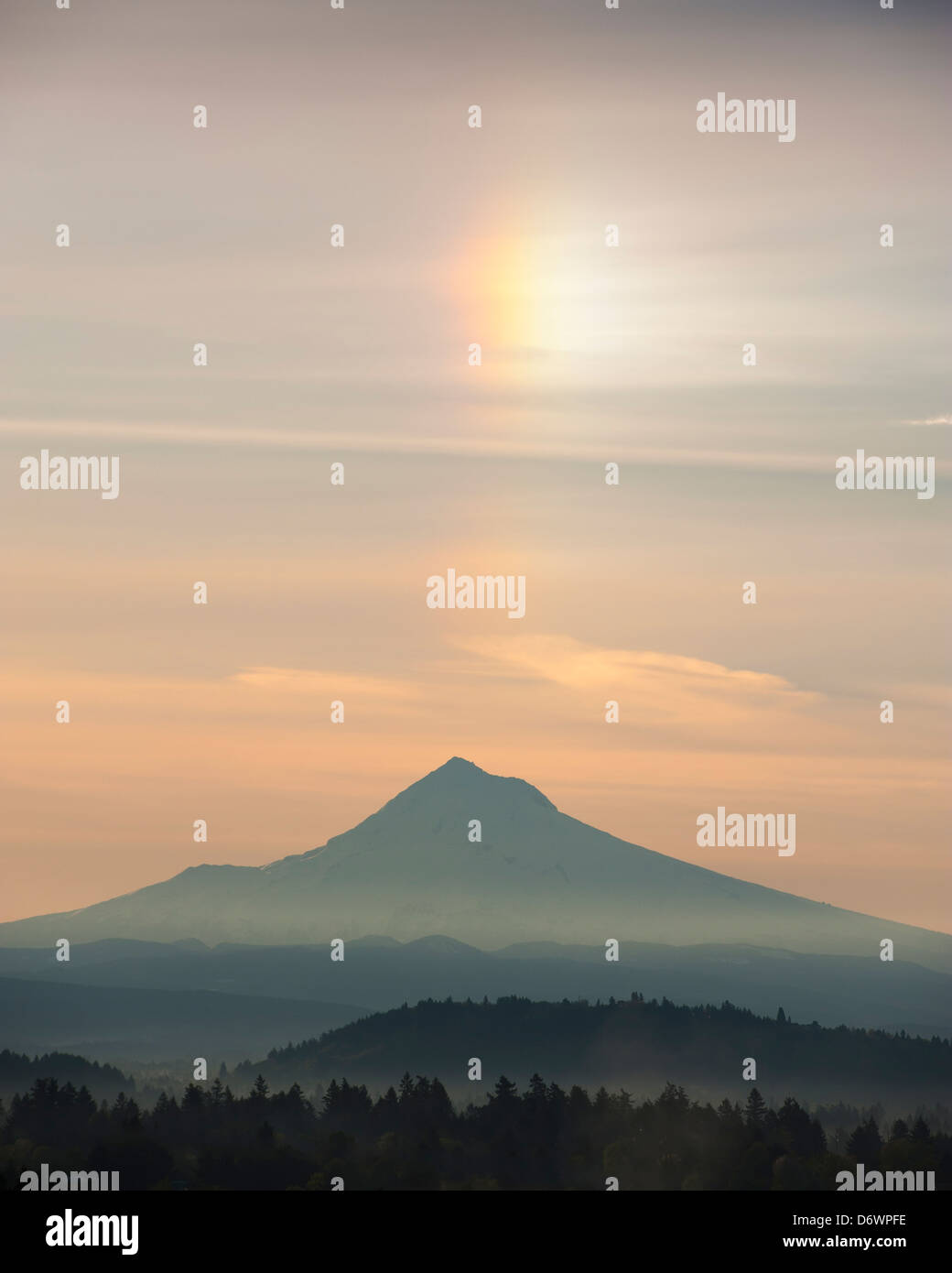 Photograph of a sun dog or mock sun or parhelia positioned above Mount Hood, a dormant volcano in America's - Stock Image
