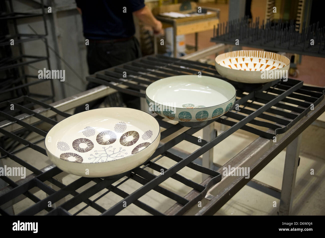 Steel enameled bowls cooling down after coming out of an enameling oven. - Stock Image