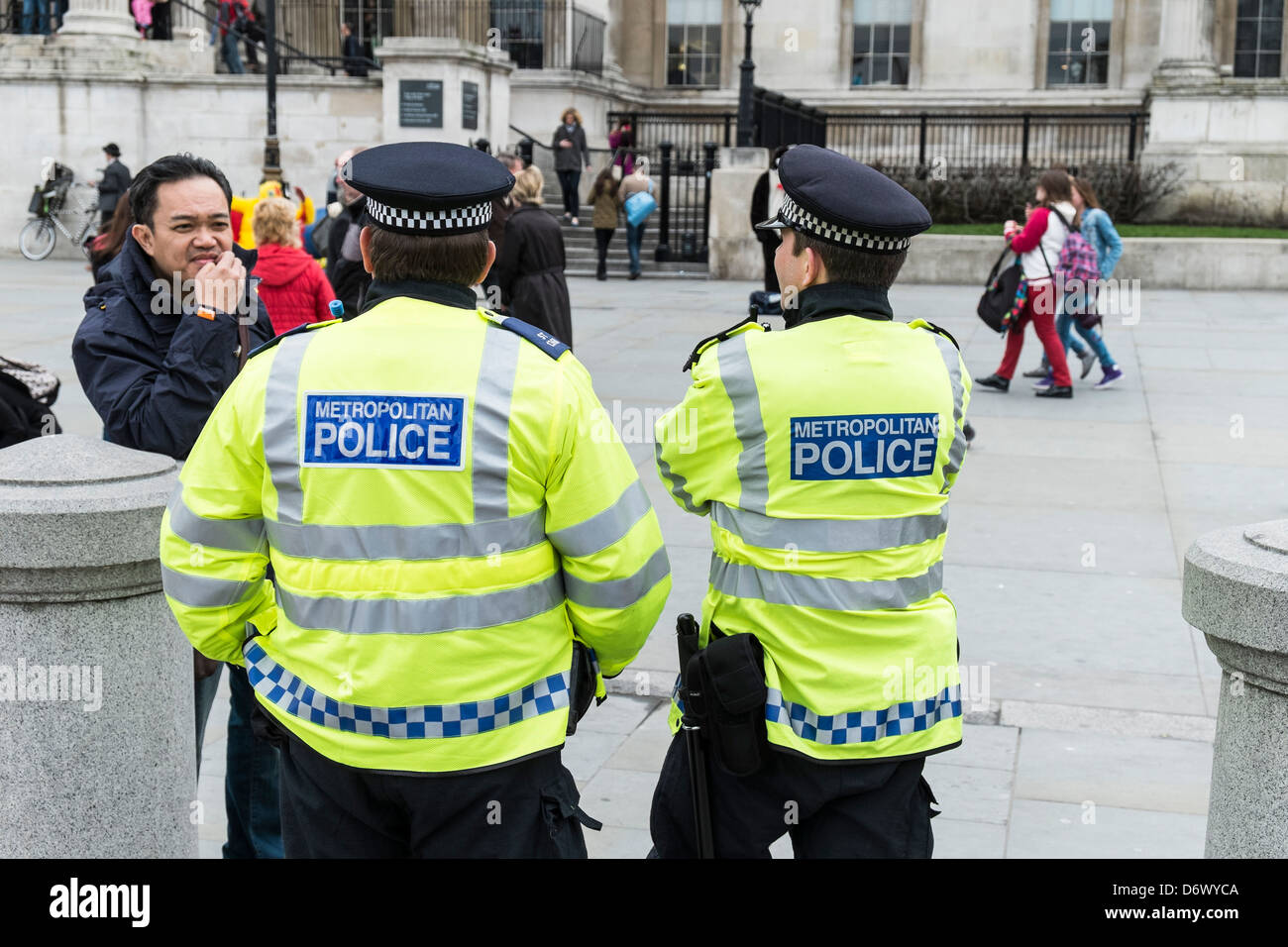 Two Metropolitan Police Officers talking to a tourist in London. - Stock Image