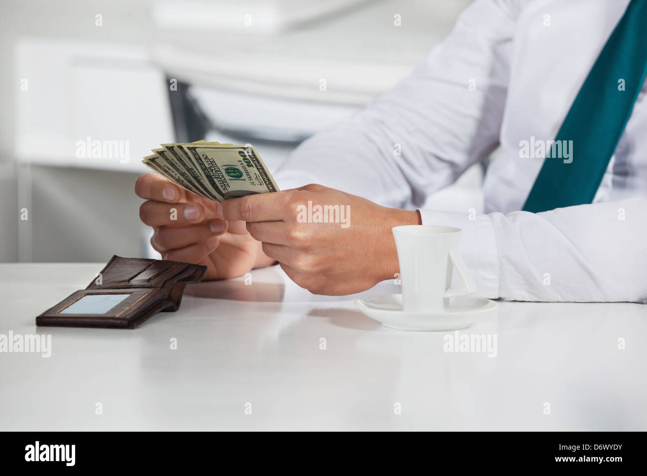 Manager counting a bunch of dollar bills in his office - Stock Image