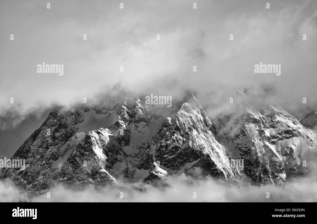 Mont Collon poking through cloud above Arolla Stock Photo