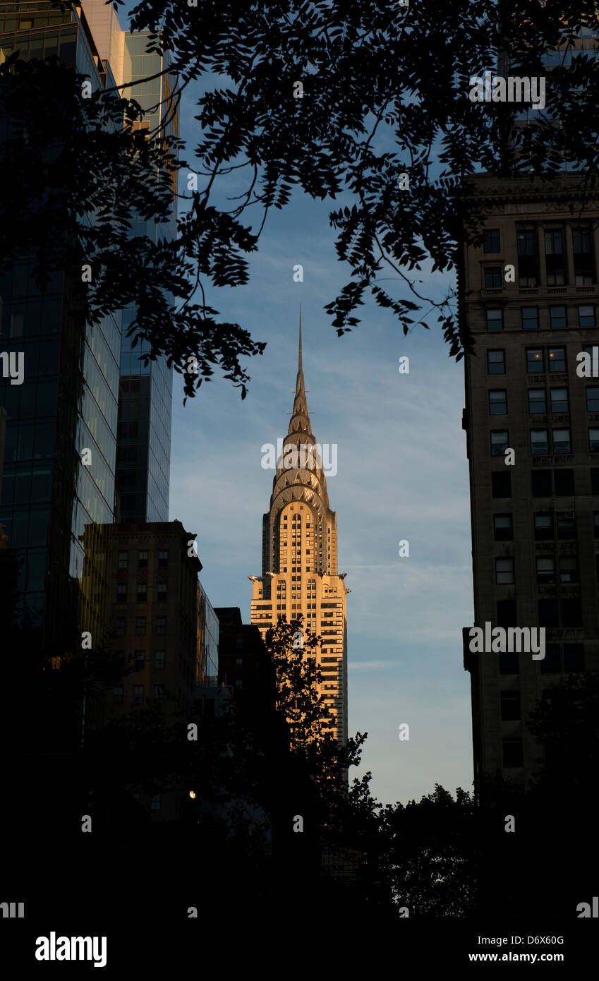 Chrysler Building framed by tree branches and buildings on a sunny day. - Stock Image