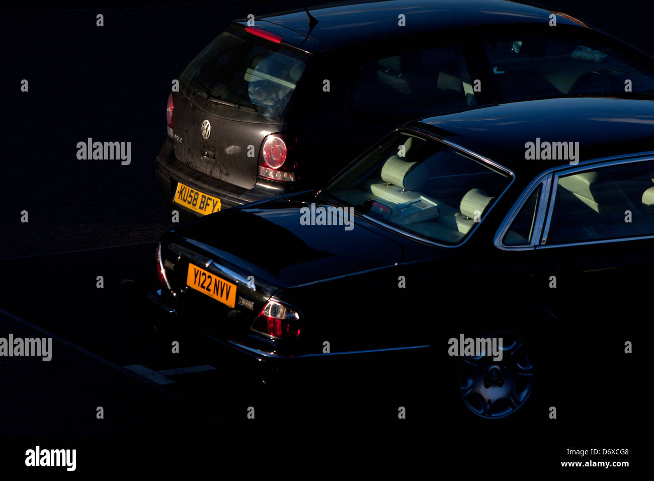Cars in a car park at dusk - Stock Image