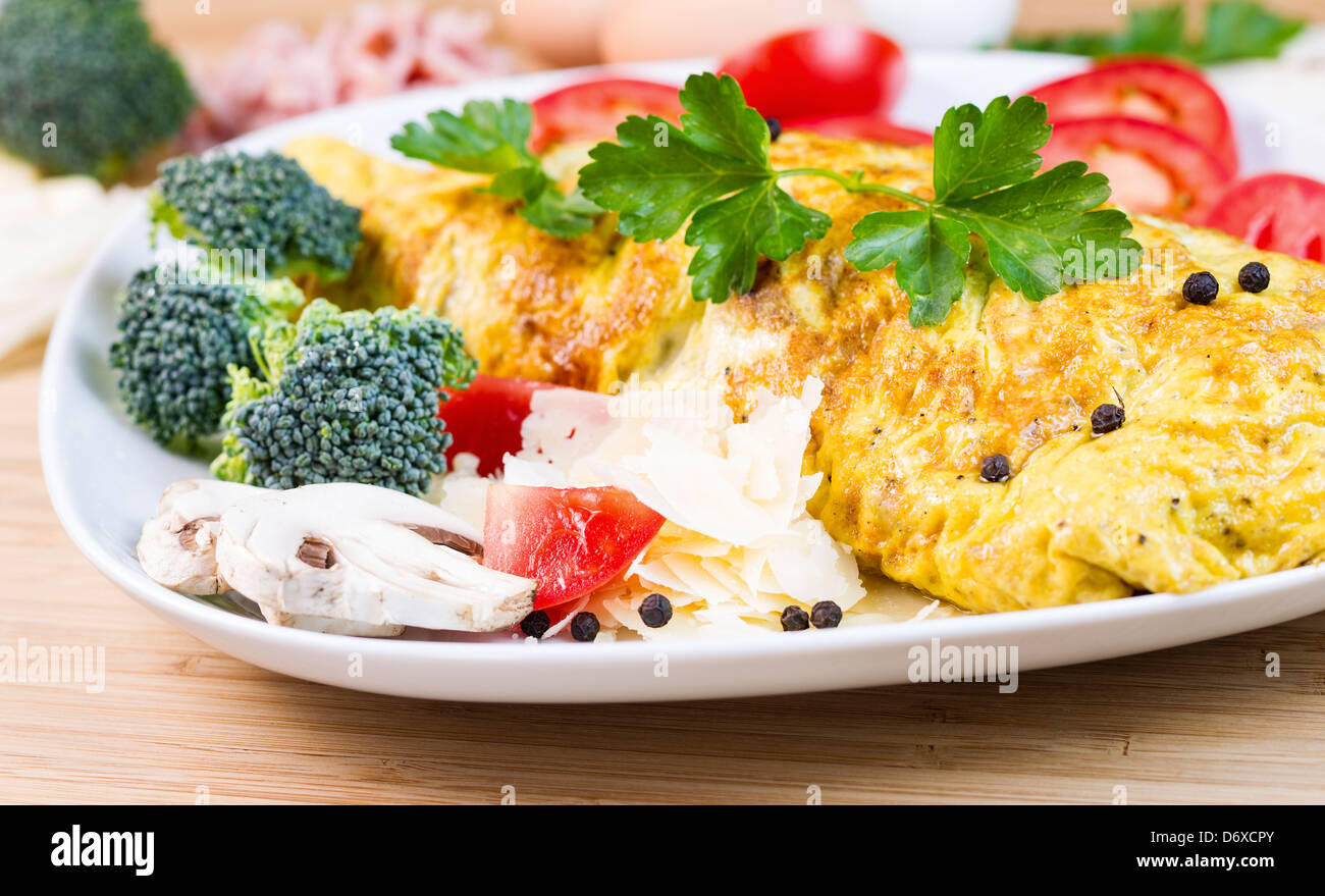 Horizontal photo of large egg omelet with mushroom, cheese, broccoli, tomato slices, pepper and parsley in white - Stock Image