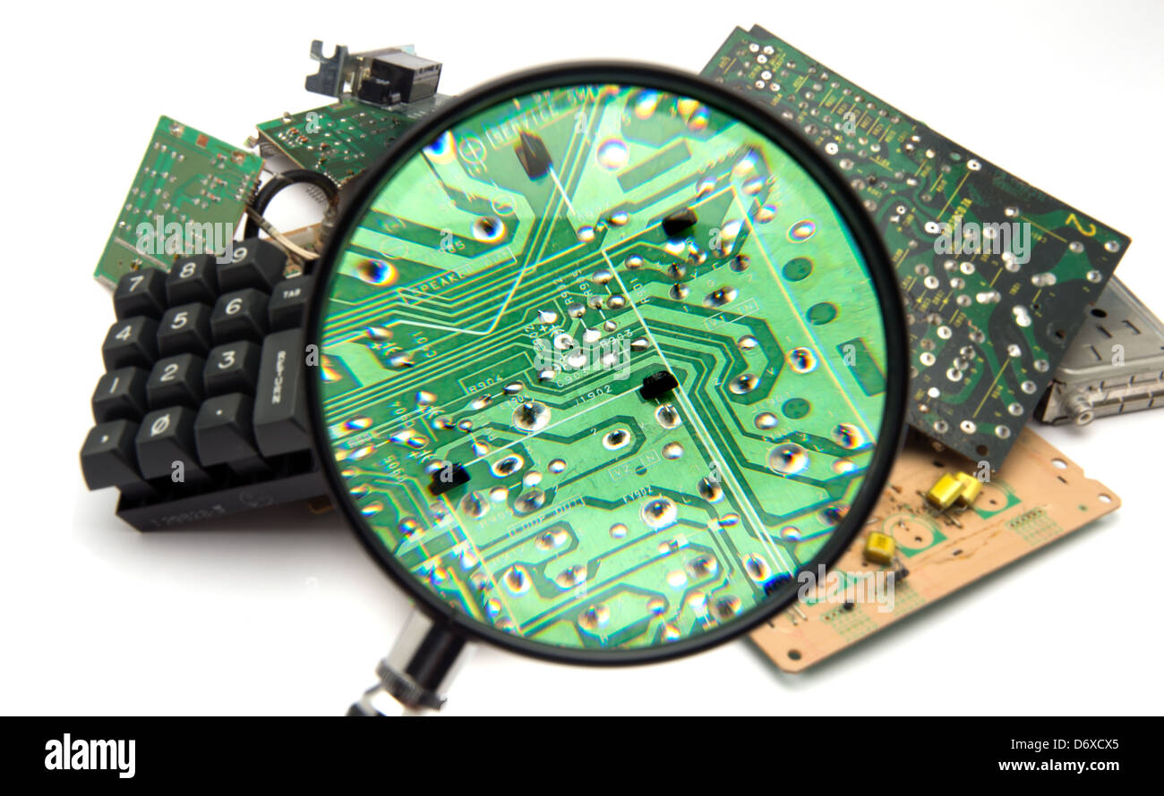 Concept photo showing digital computer parts discarded in garbage pile examined with maginfying glass Stock Photo