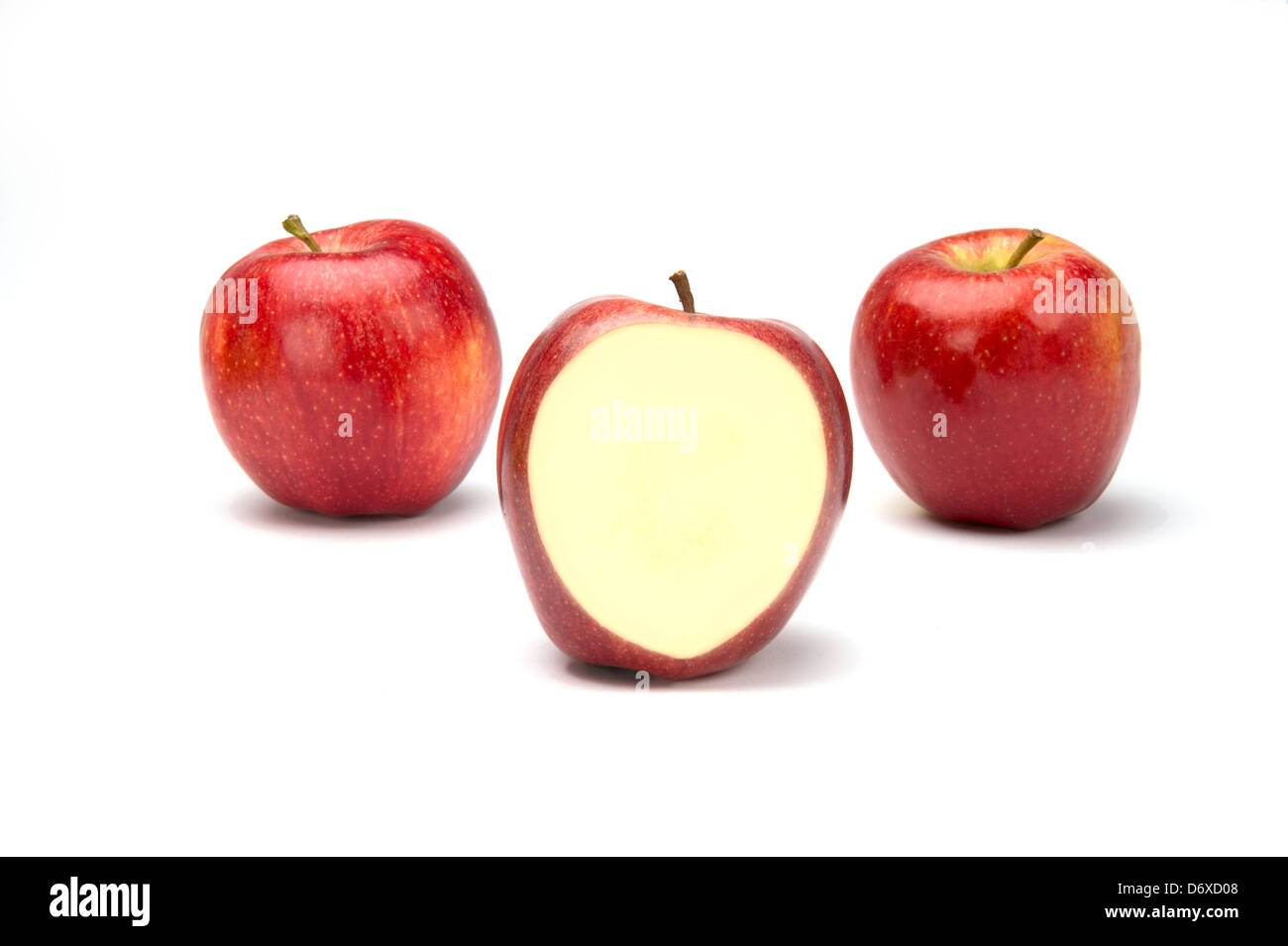 Three apples on white with the center one cut open. - Stock Image