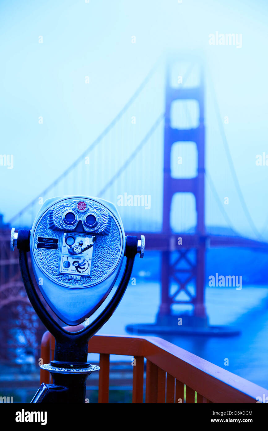 Public binoculars and Golden Gate Bridge in fog, San Francisco, California USA - Stock Image