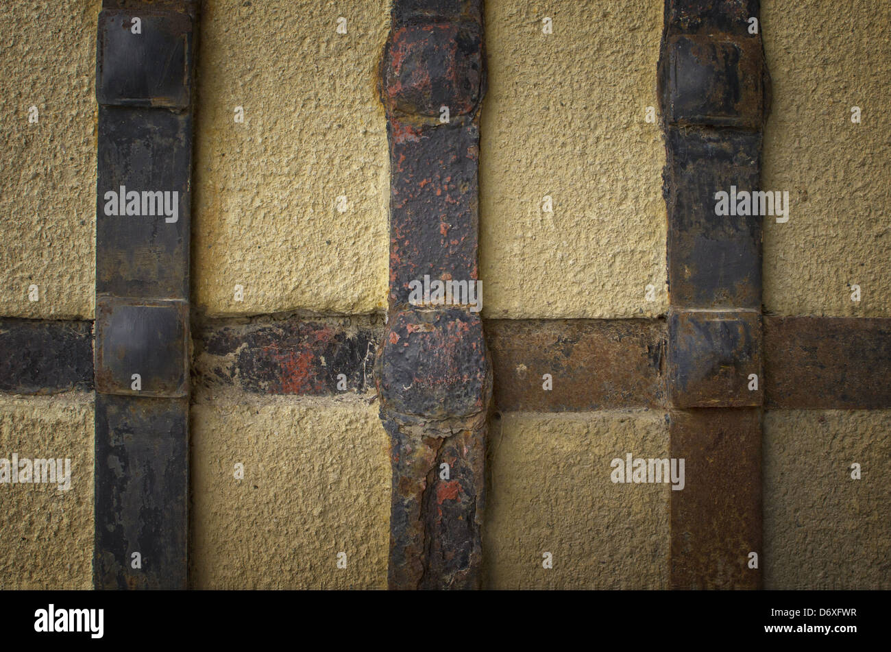 Old aged concrete church wall with iron handcraft deco work. - Stock Image