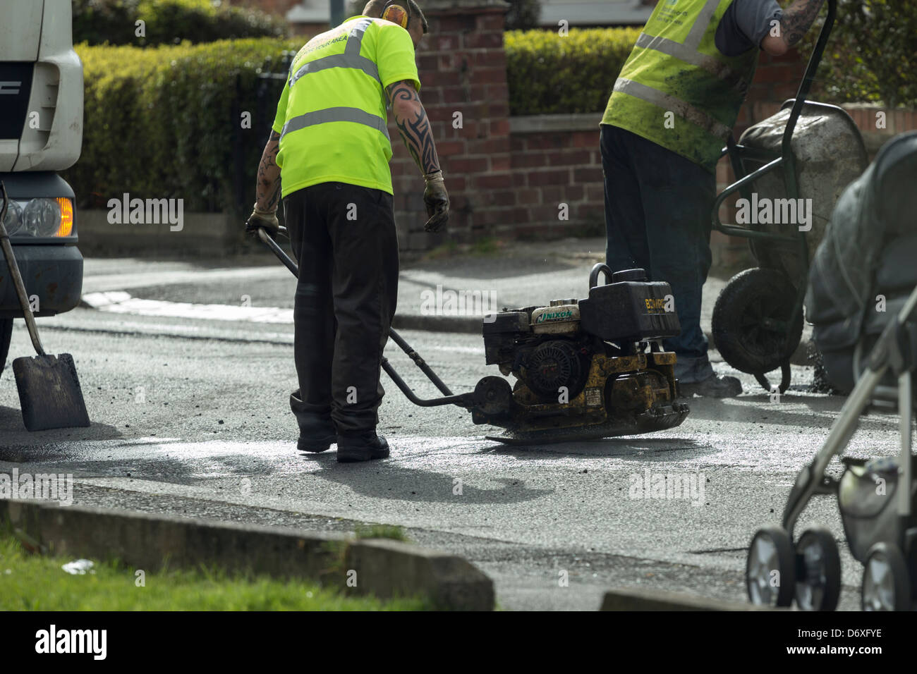 Council workers repairing potholes - Stock Image