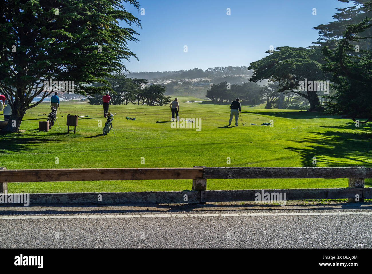 Golfers tee off at a driving range on the Monterey Peninsula near Pebble Beach in Northern California, USA. - Stock Image