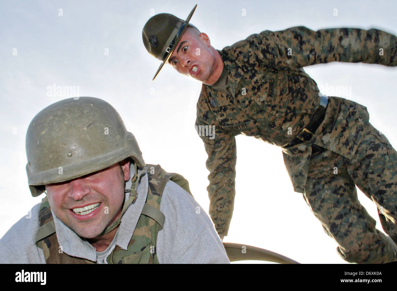 US Marine Corps drill instructors screams a civilian teacher who volunteered to tackle the bayonet assault course - Stock Image