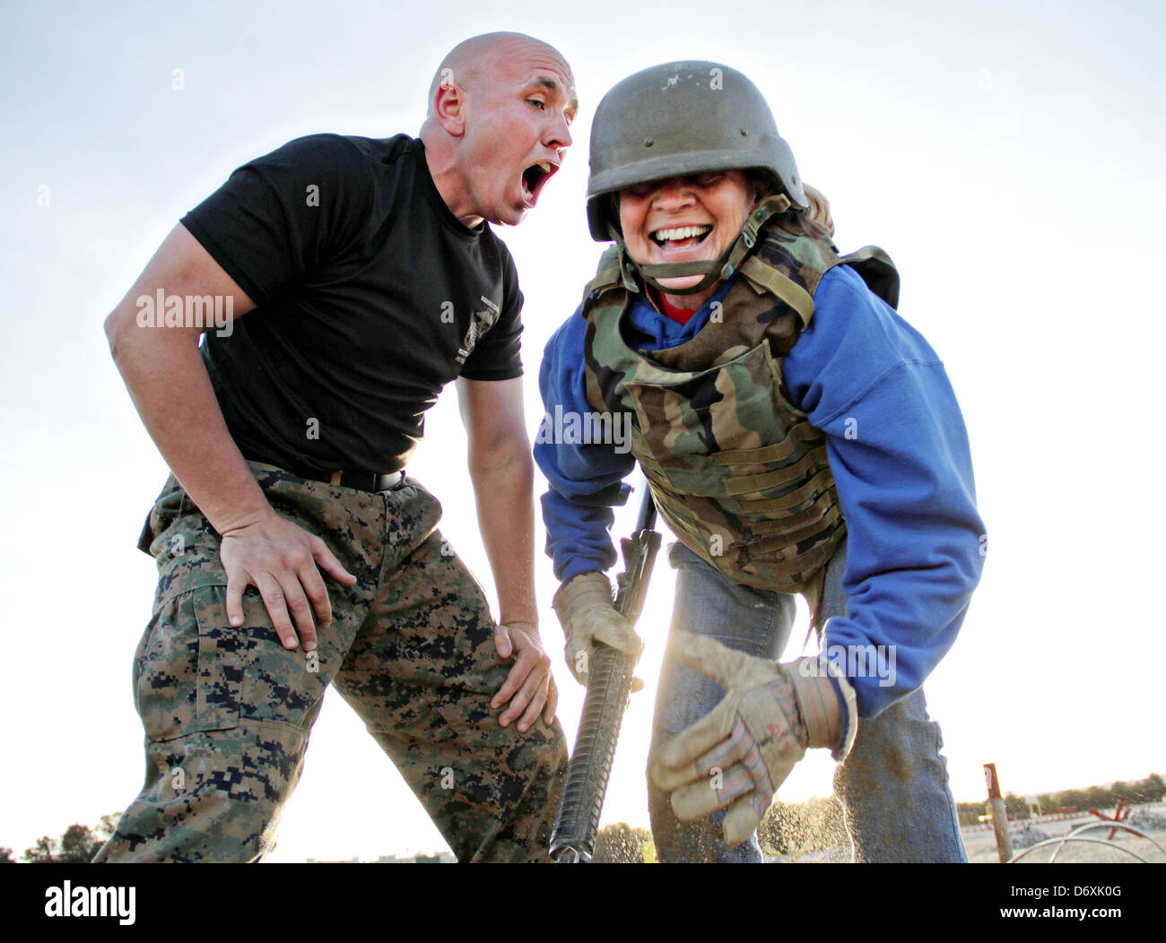 US Marine Corps drill instructors screams at a civilian teacher who volunteered to tackle the bayonet assault course - Stock Image