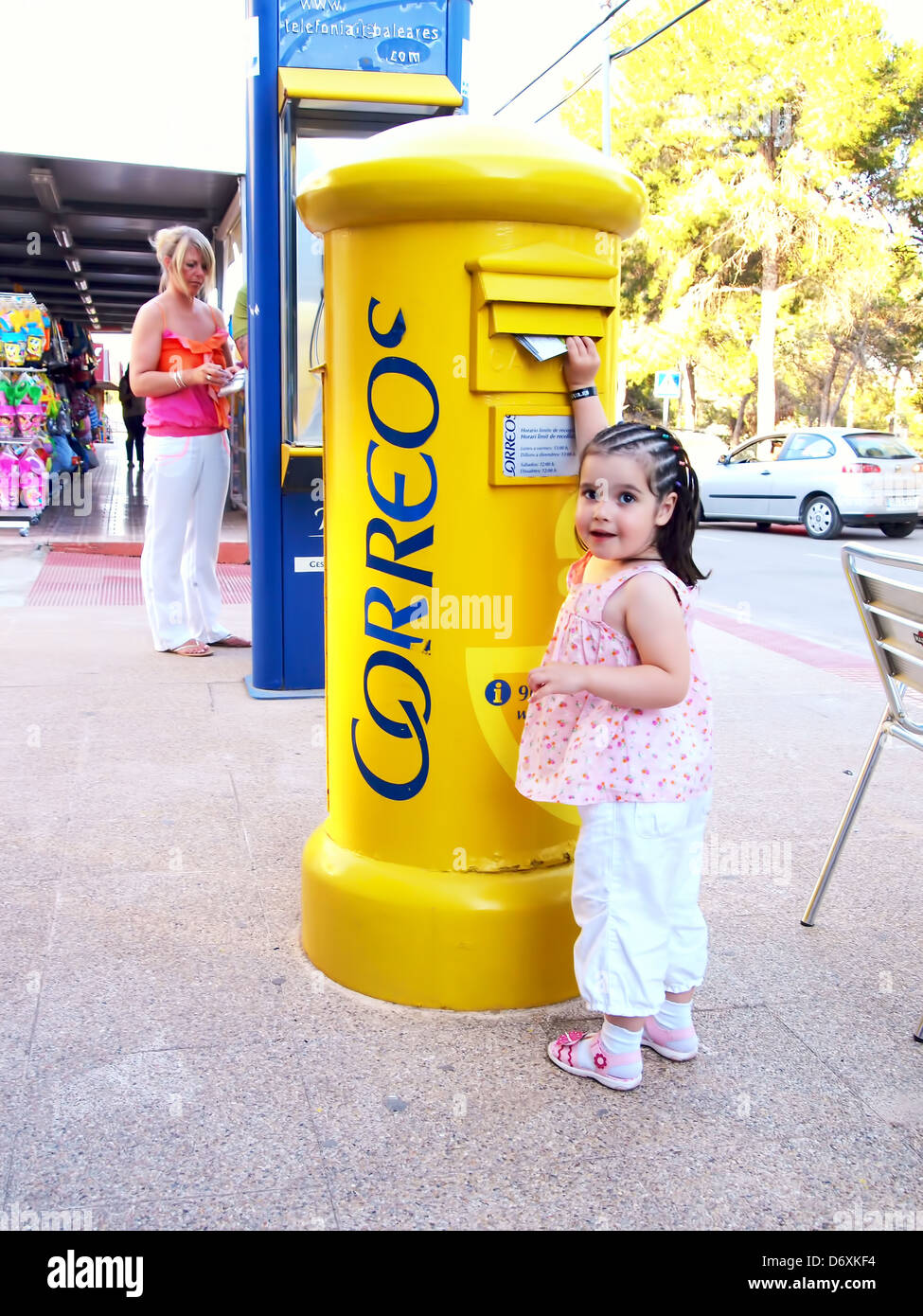 A young girl posts a letter in a yellow Spanish post box - Stock Image