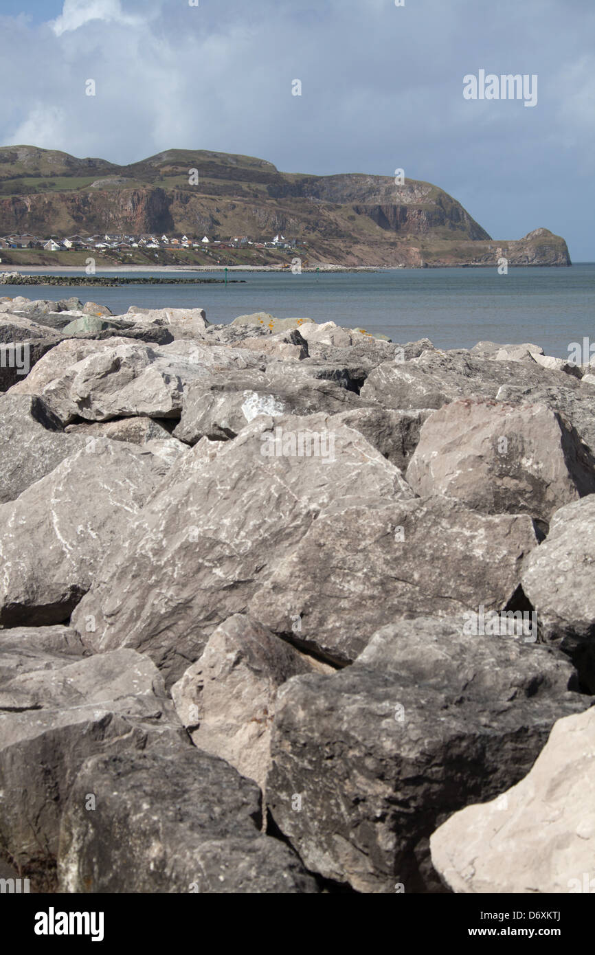 The Wales Coastal Path in North Wales. Sea defences at Rhos-on-Sea, with the Little Orme in the background. - Stock Image