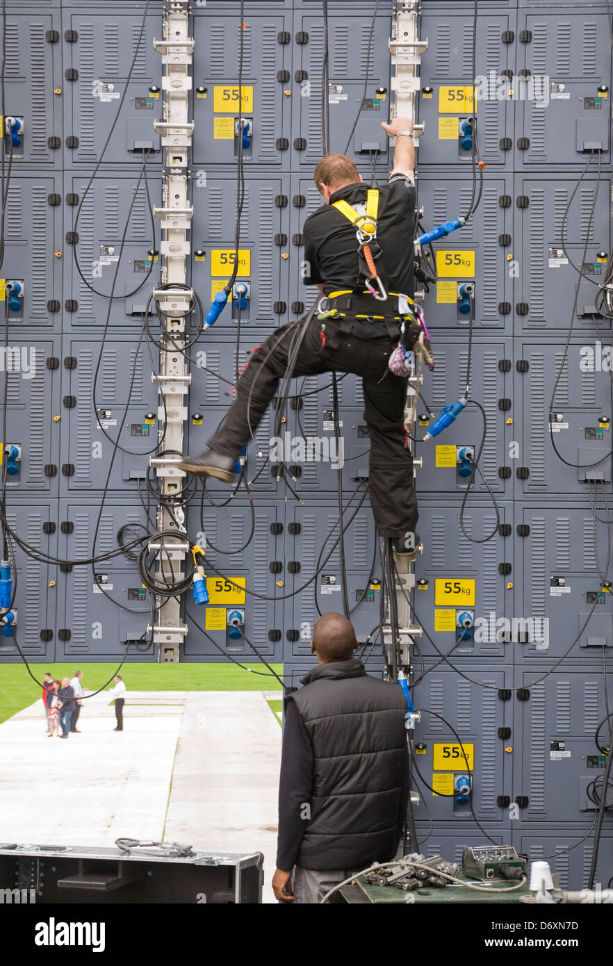 Video technician climbs a wall of video modules, prior to outdoor event. - Stock Image