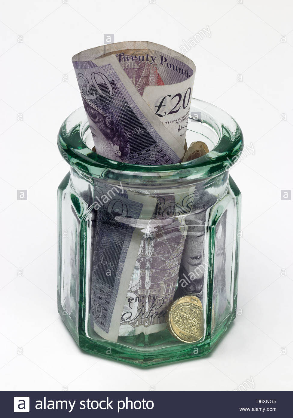 Jam jar with 20 pound notes and one pound coin in side jar - Stock Image