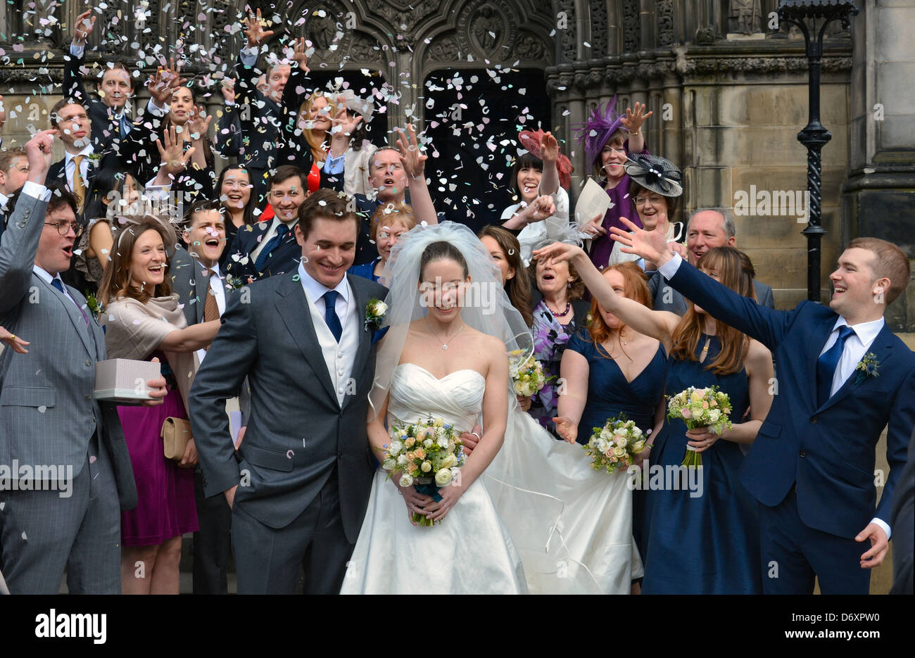 Wedding guests shower the bride and groom with confetti on the steps of St Giles Cathedral, Edinburgh. Stock Photo
