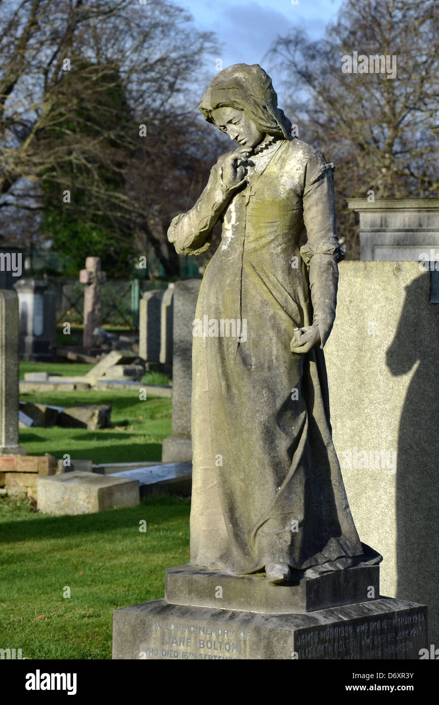 An unusual memorial in Morningside Cemetery depicting a young woman in pensive mood holding a small vial or bottle. - Stock Image