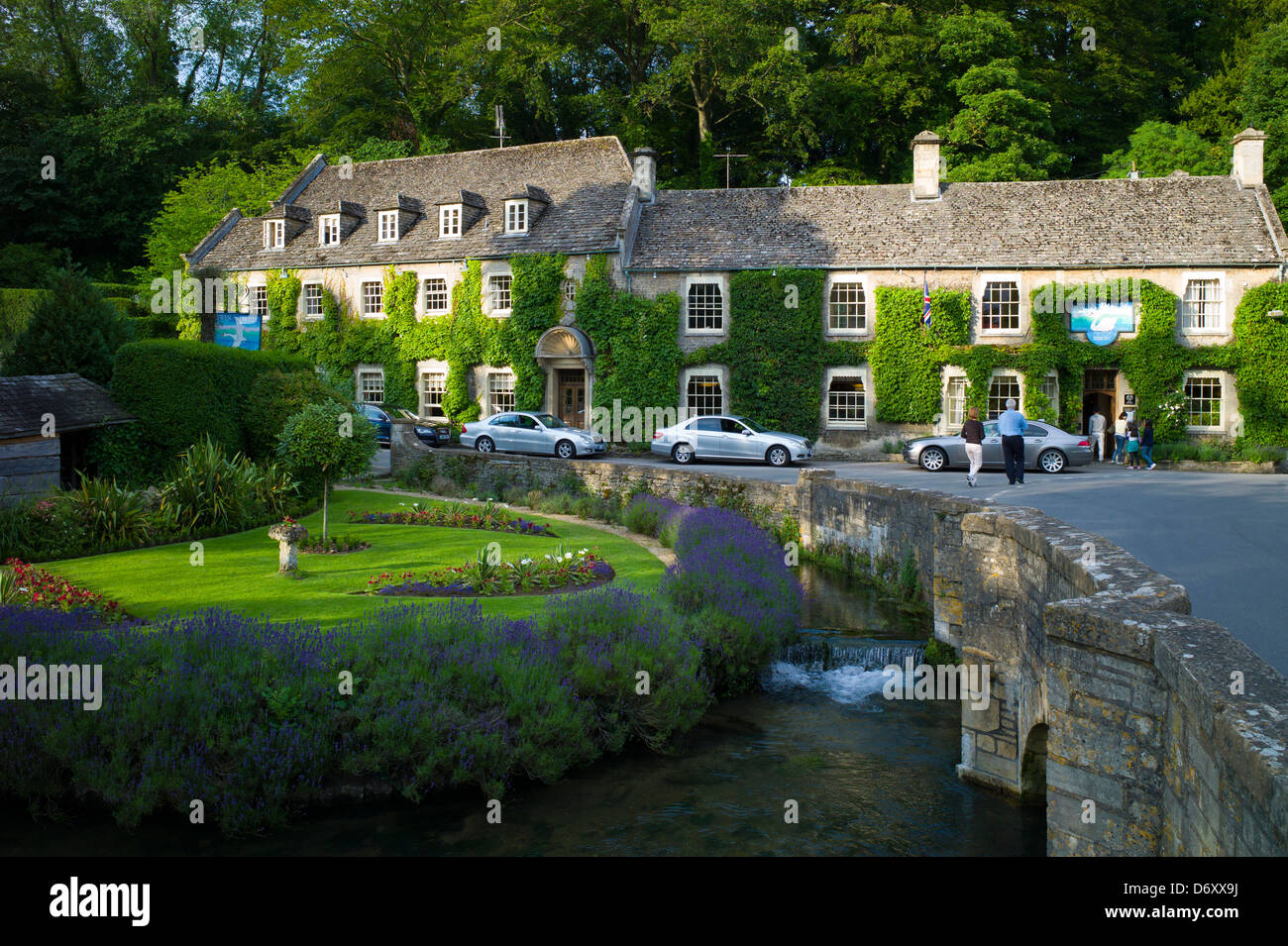 Swan Hotel and River Coln at Bibury in The Cotswolds UK. L to R: Audi A8, Mercedes C Class (2 silver cars), BMW - Stock Image