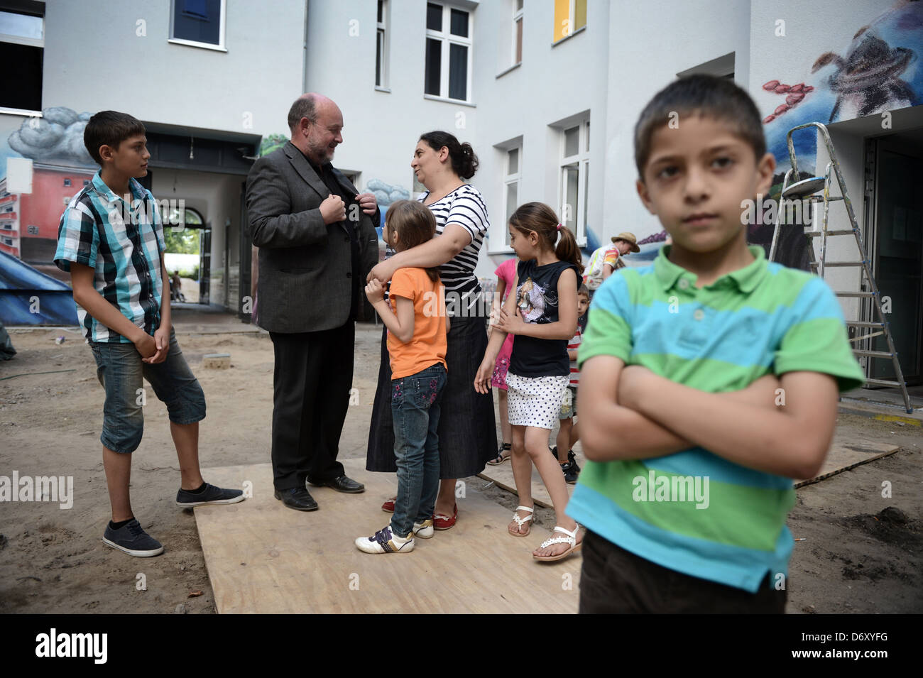 Berlin, Germany, Benjamin Marx in conversation with a Roma family in the backyard of a home in the Harz in Berlin - Stock Image