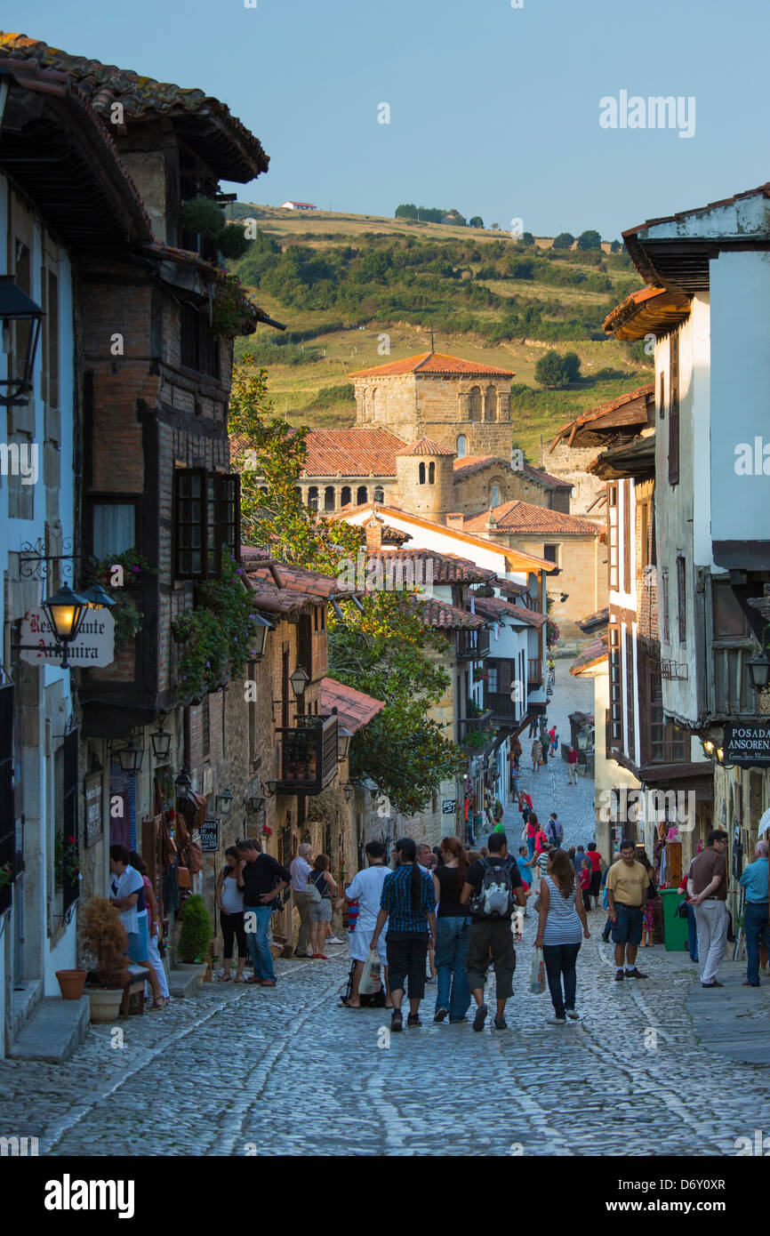 Tourists walk past medieval buildings along cobbled street of Calle Del Canton in Santillana del Mar, Cantabria, - Stock Image