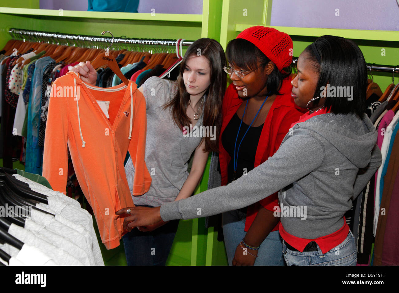 Teen girls arrange used clothing in the nonprofit woman's Express Yourself Clothing shop. St Paul Minnesota MN USA Stock Photo