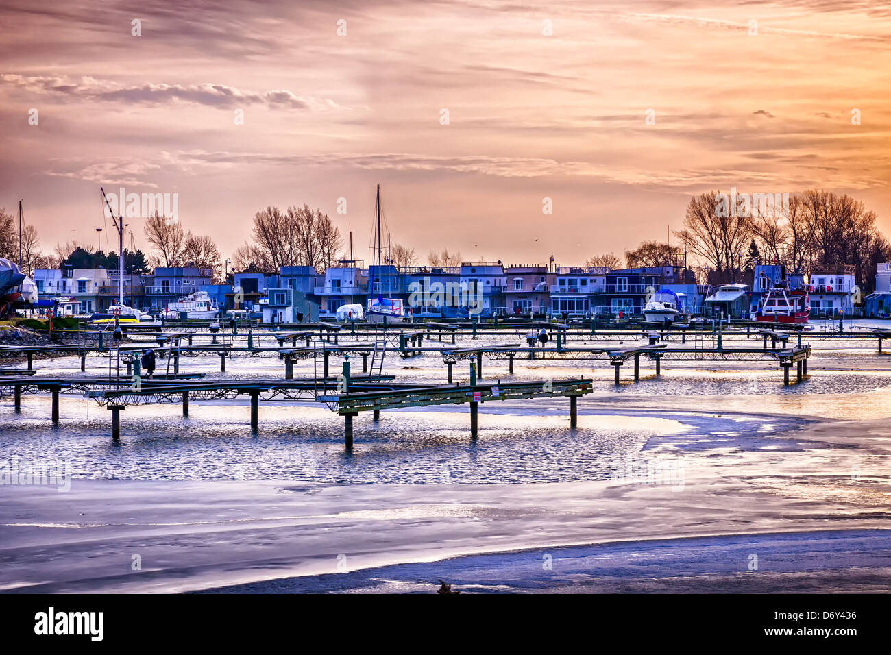 Sunset behind floating homes at Bluffers park marina in Toronto, Canada. Winter. - Stock Image